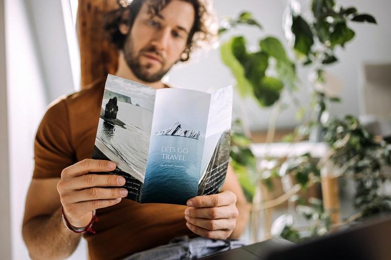 mężczyzna ogląda broszurę reklamową